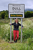 Dull - Pertshire - now officially paired with Boring - Oregon USA - Dull resident Emma Burtles cheers under the sign - picture by Donald MacLeod - 23.06.12 - 07702 319 738 - clanmacleod@btinternet.com - www.donald-macleod.com