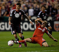 Santino Quaranta (25) of D.C. United is tackled by Ty Harden (20) of Toronto FC during the game at RFK Stadium in Washington, DC.  Toronto defeated D.C. United, 3-2.