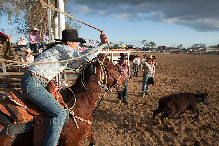 Cowgirl competing in breakaway roping competition at Mareeba Rodeo.  Breakaway roping involves the competitor on horseback lassoing a calf around its neck in the quickest time possible.    Mareeba, Queensland, Australia