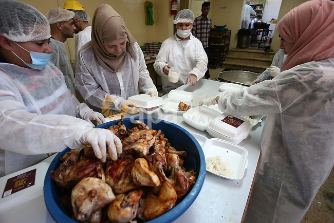 """Palestinians prepare food to be distributed for free during the holy fasting month of Ramadan in the West Bank city of Nablus, on May 11, 2019. The """"Nablus Charity Takiya"""", was founded seven years ago providing 1500 meal daily , the workers are volunteers and all food costs are provided by people of Nablus, both rich and poor can get food during the holy fasting month of Ramadan. Photo by Shadi Jarar'ah"""