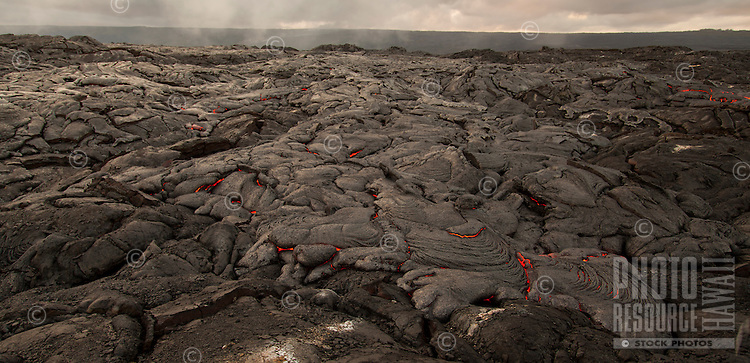 Lava surface flow slowly moves along a coastal plain, creating new land between Kalapana and Hawai'i Volcanoes National Park, Big Island.