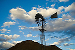 Silhouette of an Aermotor windmill against blue sky with puffy clouds, Coal Canyon, Nevada.