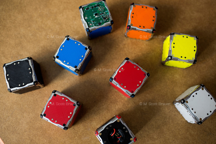 M-Block cube robots rest on a work table in the Distributed Robotics Lab in CSAIL at MIT in Cambridge, Massachusetts, USA.  The robots are 50mm cubes that can reconfigure themselves into various arrangments using self-propulsion and magnets. The work is directed by Daniela Rus, Professor of Electrical Engineering and Computer Science and Director of the Computer Science and Artificial Intelligence Laboratory at MIT.