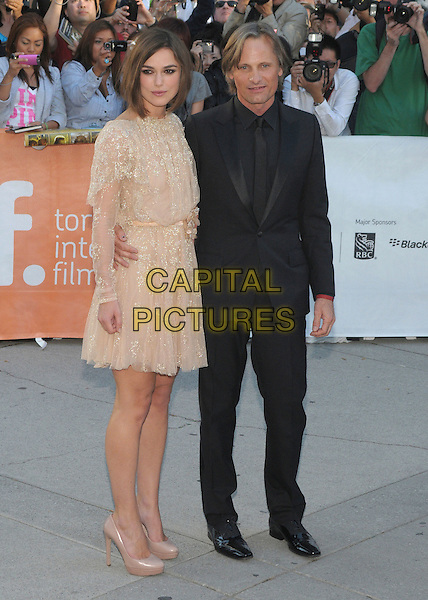 "Keira Knightley & Viggo Mortensen.""A Dangerous Method"" Premiere  - 2011 Toronto International Film Festival held at Roy Thomson Hall,  Toronto, Ontario, Canada, 10th September 2011..full length beige nude dress long sleeve sheer gold see thru through  shoes corsage flower belt black suit tie .CAP/ADM/BPC.©Brent Perniac/AdMedia/Capital Pictures."