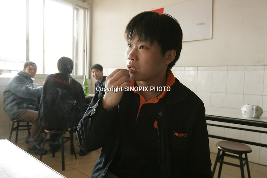 Worker Wang Zhu in a canteen outside the Osram factory in Foshan city, Guangdong Province, China, 16th January 2008. Osram China Lighting Ltd make energy saving light bulbs that are sold in the UK.