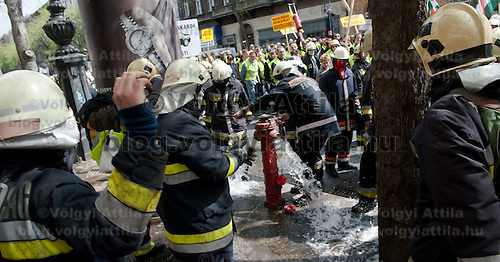 Protesting firemen open a hydrant during an anti-government rally in Budapest, Hungary on April 16, 2011..Thousands of Hungarians, including policemen and firefighters, on Saturday protested against the government's austerity measures. The government has launched a package of fiscal reforms to cut the budget deficit, including scrapping early retirement, which mostly affects law enforcement personnel.
