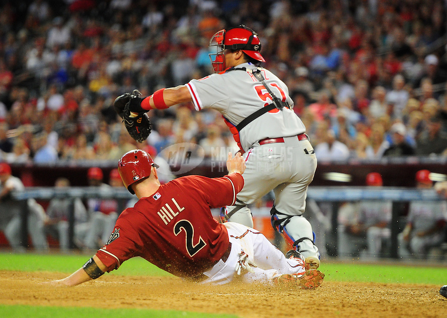 Apr. 25, 2012; Phoenix, AZ, USA; Arizona Diamondbacks base runner (2) Aaron Hill slides home to score ahead of the ball to Philadelphia Phillies catcher Carlos Ruiz in the seventh inning at Chase Field. Mandatory Credit: Mark J. Rebilas-