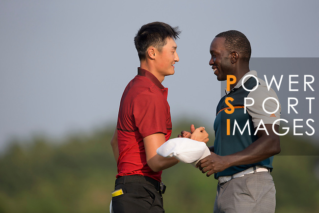 Li Haotong of China (left) shakes hands and hugs Dwight Yorke at the end of their game during the World Celebrity Pro-Am 2016 Mission Hills China Golf Tournament on 23 October 2016, in Haikou, Hainan province, China. Photo by Victor Fraile / Power Sport Images