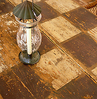 Detail of an etched glass lantern on a distressed folk-art table with a checked pattern