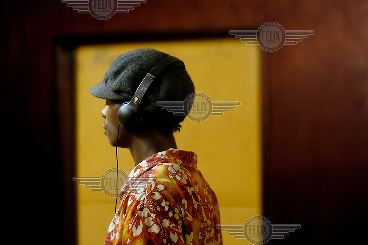 Recording artist Selassie wears a pair of headphones during a recording session at the Forensic Records Studio in Hill Station.  A new musical genre combining rap, Hip-Hop rhythms and protest lyrics which has emerged in Sierra Leone following the brutal ten year long civil war.  The music is widely regarded as conveying the 'voice of the people' and representing the conditions of the country's younger generation during its post conflict period.