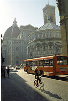 Early morning, long shadows, a girl on a bicycle passing by Brunileschi's Domo in Florence Italy