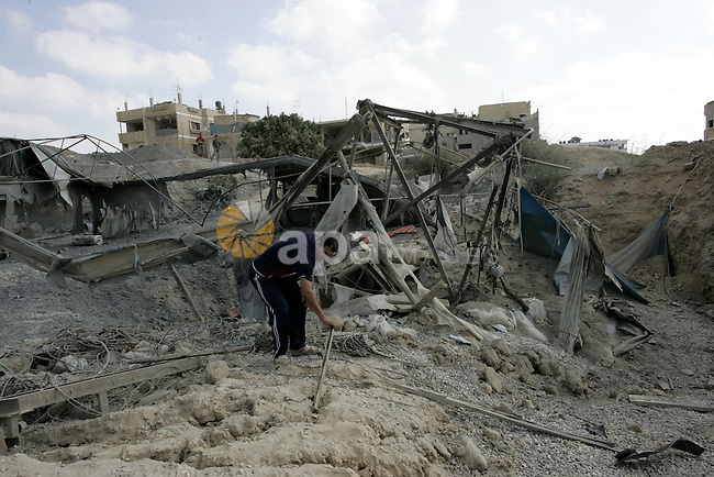 Palestinians inspect the damage outside a smuggling tunnel following an overnight Israeli airstrike in Rafah, on the border between Egypt and southern Gaza Strip, Tuesday on Aug. 16, 2011. after one Palestinian was killed and seven injured by overnight Israeli air strikes across the Gaza Strip, Palestinian medics said. The Israel Defence Forces (IDF) said the sites were targeted in response to the firing of a rocket from the Gaza Strip at the city of Beersheva. Photo by Abed Rahim Khatib