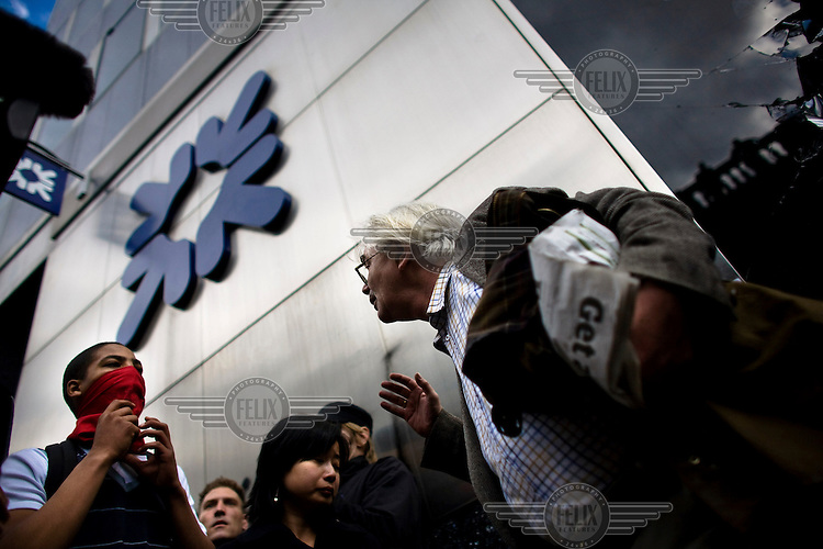 A demonstrator tries to persuade a masked youth to not break into the Royal Bank of Scotland (RBS) as thousands of protestors descended on the City of London ahead of the G20 summit of world leaders to express anger at the economic crisis, which many blame on the excesses of capitalism. RBS was the focus of anger because it had to be bailed out by the government.