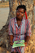 "Mbati, Zambia. Woman student in uniform holding a booklet called ""Zambia's Pride"", sitting at the foot of a tree."