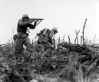 A Marine of the 1st Marine Division draws a bead on a Japanese sniper with his tommy-gun as his companion ducks for cover.  The division is working to take Wana Ridge before the town of Shuri.  Okinawa, 1945.  S.Sgt. Walter F. Kleine.  (Marine Corps)<br /> Exact Date Shot Unknown<br /> NARA FILE #:  127-N-123170<br /> WAR &amp; CONFLICT BOOK #:  1228