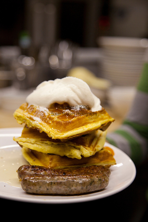 Brunch at Simpatica, a catering company that offers dinner on Friday and Saturday nights, plus a Sunday Brunch.  Located in SE Portland, Oregon. Waffles with kumquat syrup and creme chantilly.