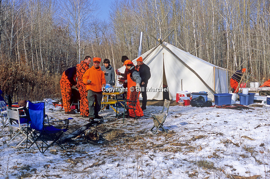 00273-043.16 White-tailed Deer Hunting: Hunters gather for lunch at tent deer camp after recent snow fall.  Camp, cold, deer, friends, comradery.