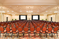 The symmetrical pattern of neatly aligned chairs in a ballroom of a Sheraton hotel.