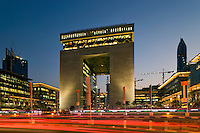 Dubai Financial District.  The Gate Building housing the DIFC, the international finance centre, and evening rush hour traffic..