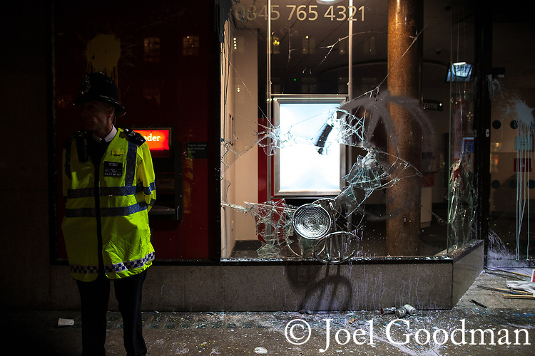 "© Joel Goodman - 07973 332324 . 26/03/2011 . London , UK . A policeman stands guard outside a branch of Santander bank , which has had its windows smashed with a chair . Hundreds of thousands of people attend an anti cuts demonstration under the banner "" March for the Alternative "" in central London , in protest at the coalition government's austerity measures . Photo credit : Joel Goodman"