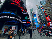 NEW YORK, NEW YORK - MARCH 03 : A screen displays the coronavirus news as people walk around Times Square in New York on March 03, 2020. New York confirms second coronavirus case, as flights cancelations and Jewish schools close over virus fears.The first person to test positive for coronavirus in the state is a 39-year-old health-care worker who arrived from Iran with her husband, the second one is an attorney who lives in Westchester County, works in Manhattan, Gov. Andrew Cuomo said. (Photo by Eduardo MunozAlvarez / VIEWpress via Getty Images)