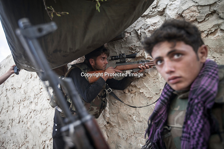 In this Thursday, Oct. 03, 2013 photo, opposition fighters belonging to AHMED KALE (not pictured) rebel group, son of MOHAMMED AHMED KALE (not pictured), mount guard at the fronline outskirst Kafr Lata, a ghost village in a top of a mountain subdued under heavy shelling and bormbardments due the fighting between opposition fighters and government forces in the Idlib province countryside of Syria. Mohammed's whole family, included his six sons with their families and four daughters, is one of two families, that refuse to leave the village despite the heavy bombardments as four of his sons fight at the frontline situated one km from home. (AP