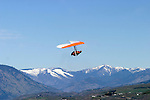 A hang glider competing in the annual spring Speed Gliding Competition in Chelan, Washington, flies against a backdrop of snowy mountains.