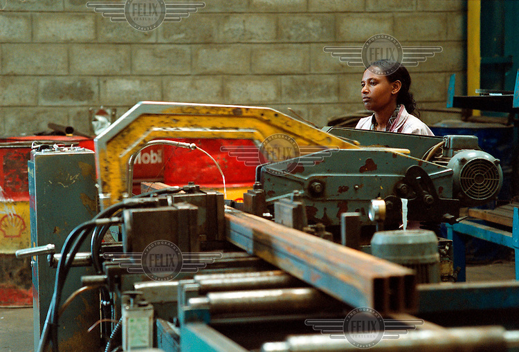 Female worker using a metal saw in the Mesfin Industrial Engineering factory, which produces oil containers for Shell. Mesfin Industrial Engineering is part of the Effort Association, which belongs to the TPLF, the main political party of Tigray.