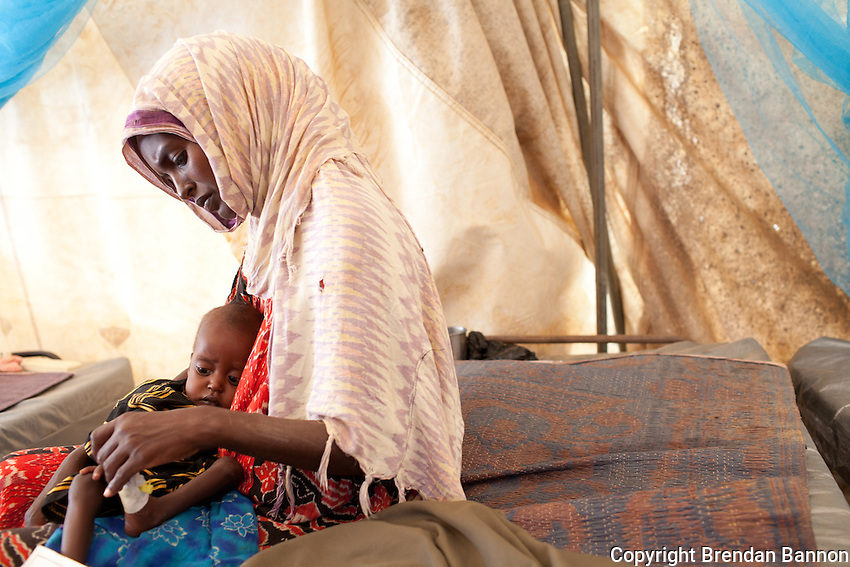 "Fatuma Badel fled Buale, Somalia with 8 children after leaving her sick husband. ""he became sick and I couldn't carry him. I don't know if he is alive or dead. This one, my youngest was like a dead person when i arrived. Now I thank God I can hear him cry again."" She has been  3 days in the MSF hospital with her baby Mohamud who arribvedseverely malnourished. At nine months old he weighs 4.3 KG. Dadaab refugee camp, kenya July 22, 2011. Photo: Brendan Bannon"