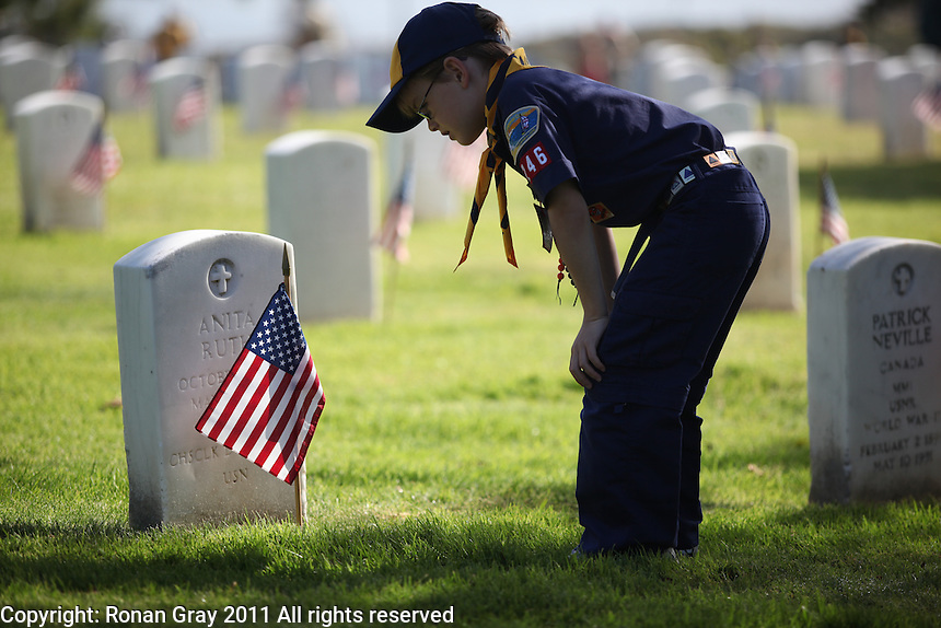 Fort Rosecrans National Cemetery, San Diego, CA.  May 28th, 2011:  Sean Gray (7) of Pacific Beach Cub Scout Pack 246 reads a grave stone after planting a flag in Fort Rosecrans National Cemetery.   Hundreds of Cubs, Boy Scouts, Girl Scouts and their parents spread out across the cemetery to plant flags on each grave for Memorial Day 2011.
