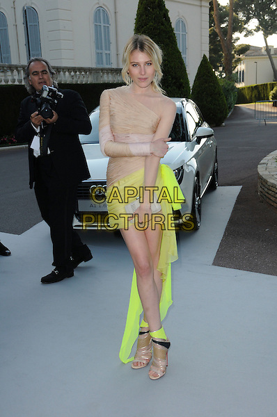 DREE HEMINGWAY.arrivals at amfAR's Cinema Against AIDS 2010 benefit gala at the Hotel du Cap, Antibes, Cannes, France during the Cannes Film Festival.20th May 2010.amfAR full length beige neon yellow dress ruched silk mini sandals one shoulder nude sleeve open toe shoes boots ankle.CAP/CAS.©Bob Cass/Capital Pictures.