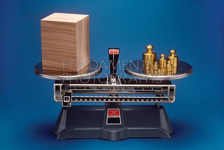 EQUAL MASS COMPARISON<br /> Double Pan Balance Scale<br /> A double pan balance scale compares the equivalent mass of a wooden block at left and a collection of weights on the right.