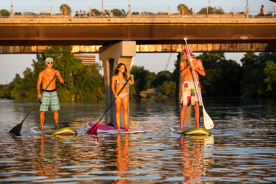 A group of friends enjoy a beautiful summer's day while on Stand-Up Paddle Boards (SUP) on Lady Bird Lake in Austin, Texas