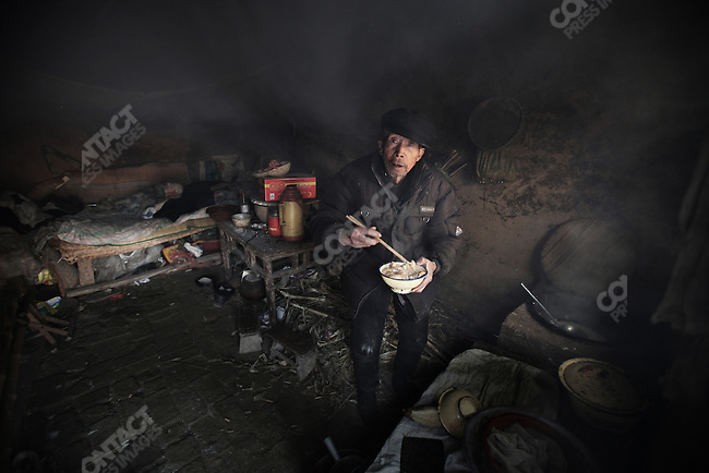 Impoverished Gao Wanshun, whose wife died of cancer, in the village of Zhangyuzhuang along the polluted Hong River in Xiping County. Henan Province. April 3, 2009.