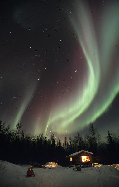 The aurora borealis, or northern lights, dance in the night sky above a cabin in Alaska's interior near Fairbanks.