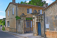 The Chateau Roc de Cambes with stone wall iron gate and stone gate posts with the name carved. Blue doors and yellow house  Cotes de Bourg  Bordeaux Gironde Aquitaine France