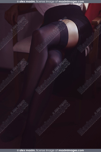 Closeup of sexy legs in black stockings of a woman sitting in a chair wearing a skirt with long cut
