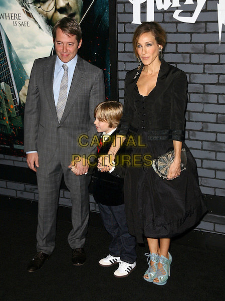MATTHEW BRODERICK, JAMES WILKIE BRODERICK & SARAH JESSICA PARKER .The premiere of 'Harry Potter and the Deathly Hallows - Part 1' at Alice Tully Hall in New York City, New York,  NY, USA, 15th November 2010 ..full length family husband wife son holding hands grey gray suit blue shirt tie black dress jacket skirt ruched shoes platform green turquoise shooboots peep toe   clutch bag cut out ankle boots booties .CAP/ADM/PZ.©Paul Zimmerman/AdMedia/Capital Pictures.