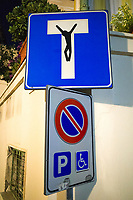 Italy. Liguria Region. Bordighera. Old town. Traffic sign. A dead end sign tagged with a drawing of Jesus Christ on the cross. The crucifixion of Jesus is collectively referred to as the Passion, Jesus' suffering and redemptive death by crucifixion are the central aspects of Christian theology concerning the doctrines of salvation and atonement. Other signs, parking allowed only for handicapped people. Liguria is a region of north-western Italy. Bordighera is a town and comune in the Province of Imperia. 27.07.2020 © 2020 Didier Ruef