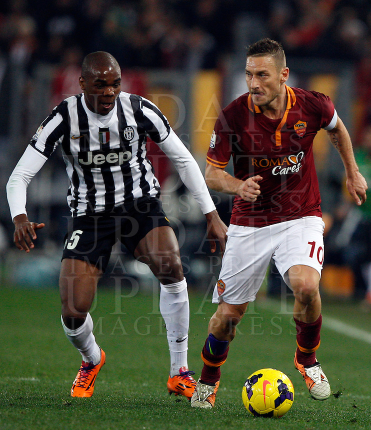 Calcio, quarti di finale di Coppa Italia: Roma vs Juventus. Roma, stadio Olimpico, 21 gennaio 2014.<br /> AS Roma forward Francesco Totti is challenged by Juventus defender Angelo Ogbonna, left, during the Italian Cup round of eight final football match between AS Roma and Juventus, at Rome's Olympic stadium, 21 January 2014.<br /> UPDATE IMAGES PRESS/Riccardo De Luca