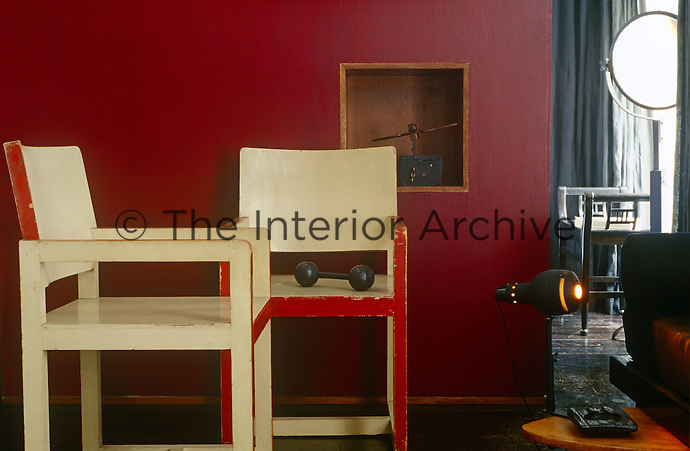 The simple and elegant lines of a pair of matching vintage armchairs as seen against a wall painted deep cherry-red in the guest room
