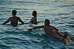 Female Surfer and couple wading in the water at Waikiki Beach, Honolulu, Oahu, Hawaii