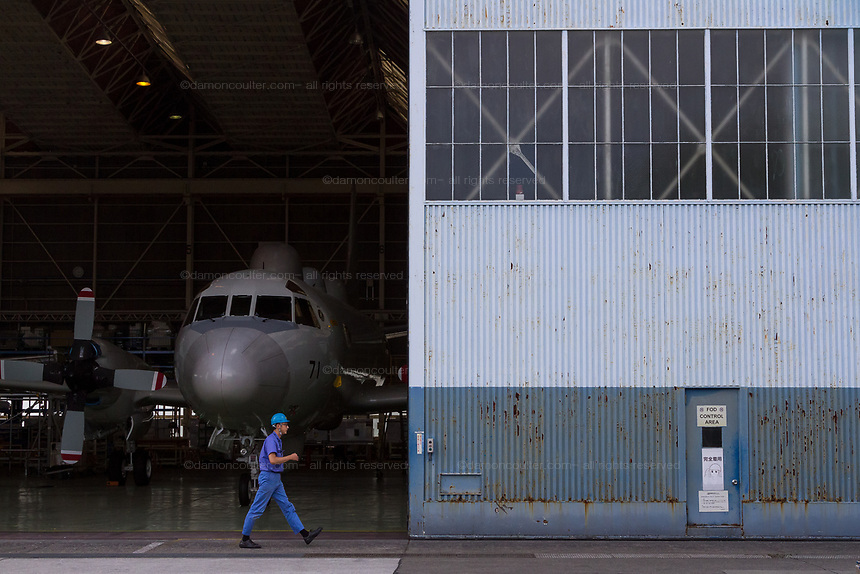 A workman walks past a Lockheed EP3 Orion ELINT signals reconnaissance aircraft being serviced in a hanger on Naval Air Facility, Atsugi airbase Yamato, Kanagawa, Japan. Wednesday July10th 2019