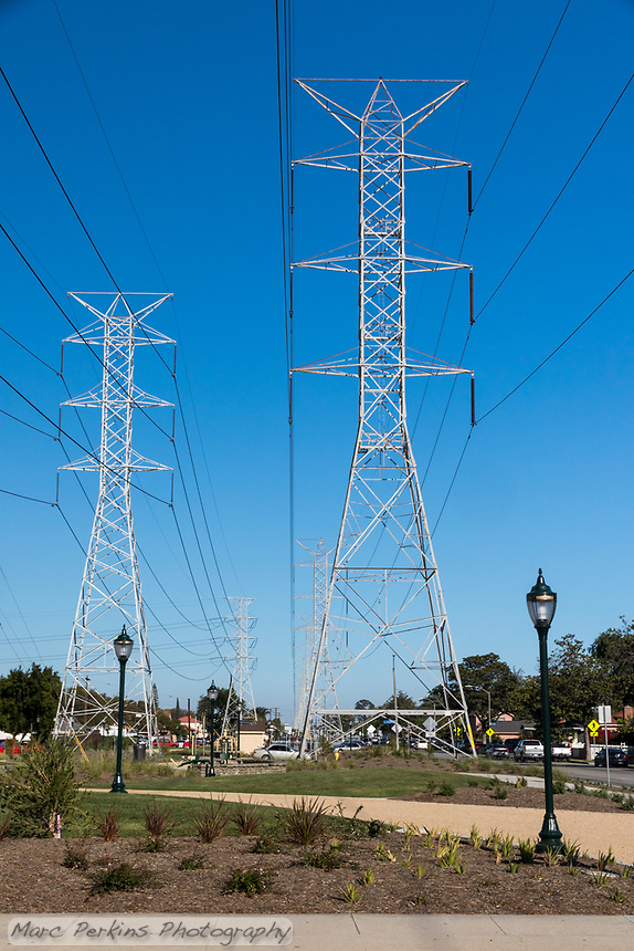 Giant electrical towers stand over State Street Park; the park's decomposed granite trails, lighting, and landscaping are all visible.