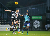 Haydn Hollis of Notts Co holds onto Adebayo Akinfenwa of Wycombe Wanderers during the Sky Bet League 2 match between Notts County and Wycombe Wanderers at Meadow Lane, Nottingham, England on 10 December 2016. Photo by Andy Rowland.