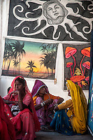 Ladies sitting in front of Wall hangings at Pushkar fair. Rajasthan, India.