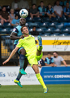 Luke Prosser of Colchester United and Adebayo Akinfenwa of Wycombe Wanderers tussle during the Sky Bet League 2 match between Wycombe Wanderers and Colchester United at Adams Park, High Wycombe, England on 27 August 2016. Photo by Liam McAvoy.