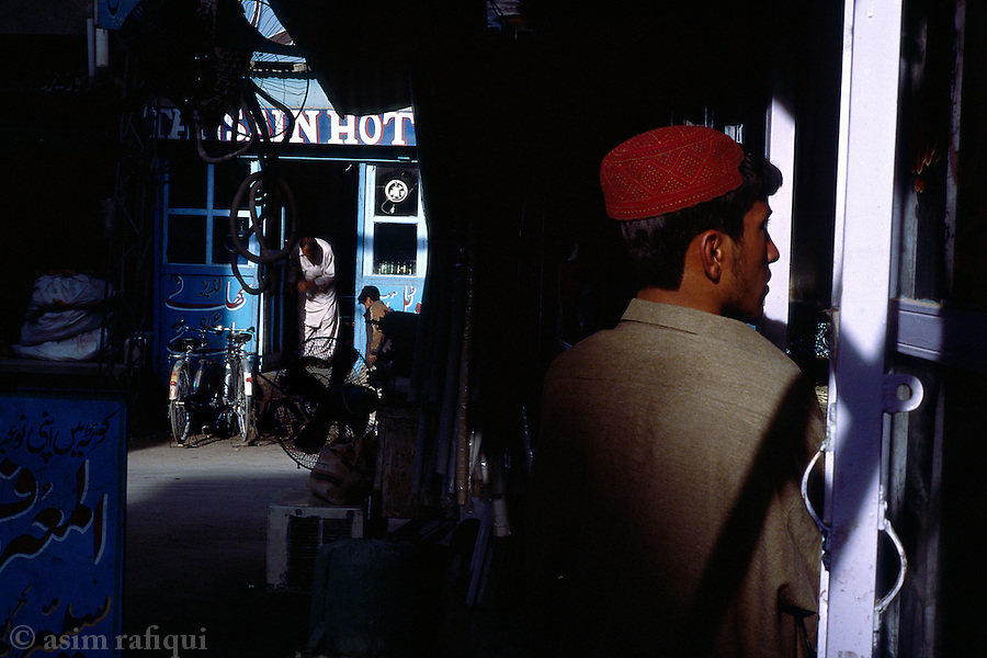 Market scene in the city of Quetta - young man standing outside a restaurant showing Indian movies while in the back ground another hotel-keeper prepares for the morning's customers.