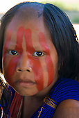 Pará State, Brazil. Aldeia Pukararankre (Kayapo). Girl with shaved parting, face and body paint and bead adornments.