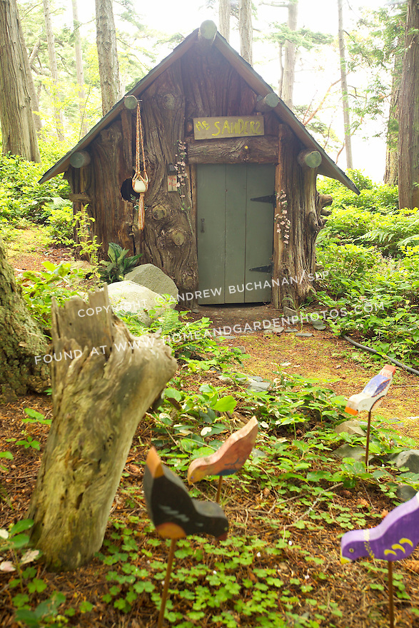 A charming Winnie-the-Pooh inspired, wooden playhouse sits at the end of a path in the woods.